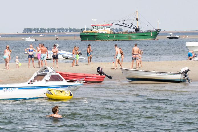Het beeld op de zandbank is hetzelfde als op ieder ander strand. Alleen liggen hier allemaal boten rondom de zandplaat.
