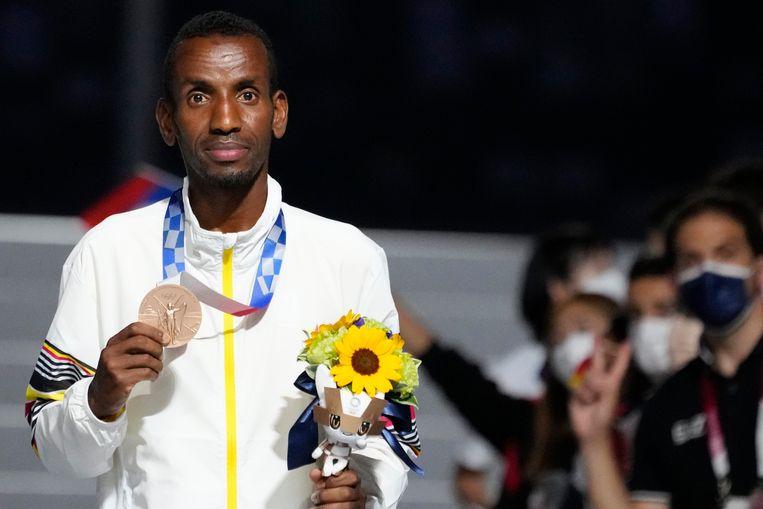 Marathonloper Bashir Abdi toont zijn bronzen plak aan de fotografen. Beeld AP