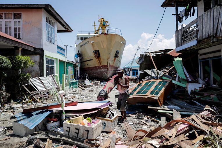 Een man uit Wani haalt uit de puinhoop van wat eens zijn huis was nog wat bruikbare spullen. Het gestrande schip maakt het surreële plaatje compleet.  Beeld EPA