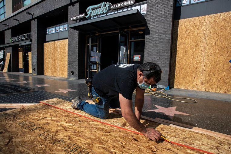 Eigenaars van winkels timmeren hun etalages dicht omdat ze geweld in de straten vrezen.  Beeld Photo News