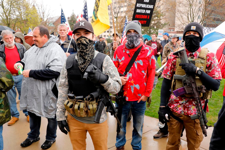 Gewapende mannen doen mee aan een demonstratie in Lansing, de hoofdstad van Michigan,  tegen beperkende coronamaatregelen.  Beeld AFP