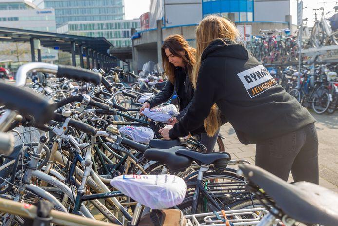Lotte Heemskerk (l) en Marleen Tempelaars voorzien een paar honderd fietsen op het station van een zadelhoesje.