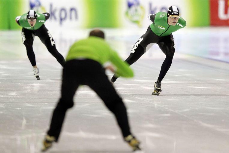 Sven Kramer in actie tegen Jan Blokhuijsen tijdens de kwalificatie  op de 5000 meter. Op de voorgrond schaatscoach Gerard Kemkers. Beeld anp