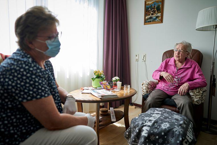 Een bewoonster van verpleeghuis Leilinde van Woonzorgcentra Haaglanden krijgt bezoek. Verpleeghuizen mogen weer bezoek ontvangen, maar wel volgens strikte regels om zo de kans op besmettingen met het coronavirus zo laag mogelijk te houden.  Beeld ANP