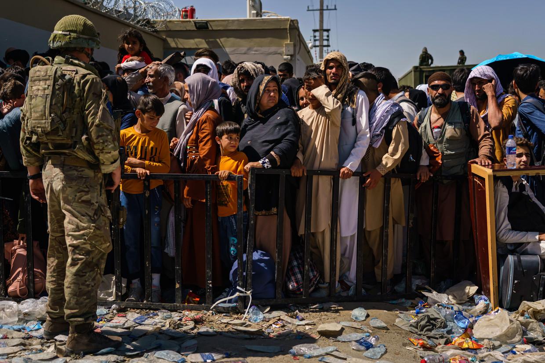 Britse en Amerikaanse militairen bewaken de toegang tot het vliegveld van Kabul. Om sneller te worden toegelaten, gaf de Nederlandse overheid de instructie oranje kledingstukken te dragen. Beeld Marcus Yam /LA Times via Getty