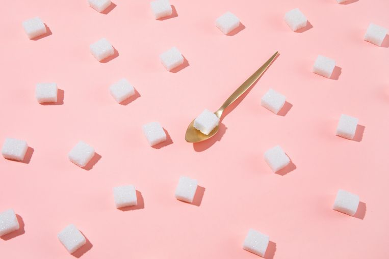 Geometrical pattern with white sugar cubes and a teaspoon on pastel pink background Beeld Getty Images