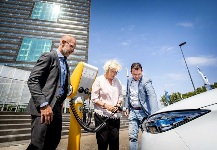Directeur-generaal Michèle Blom (M) van Rijkswaterstaat sluit als eerste een elektrische auto aan op de laadpraatpaal.