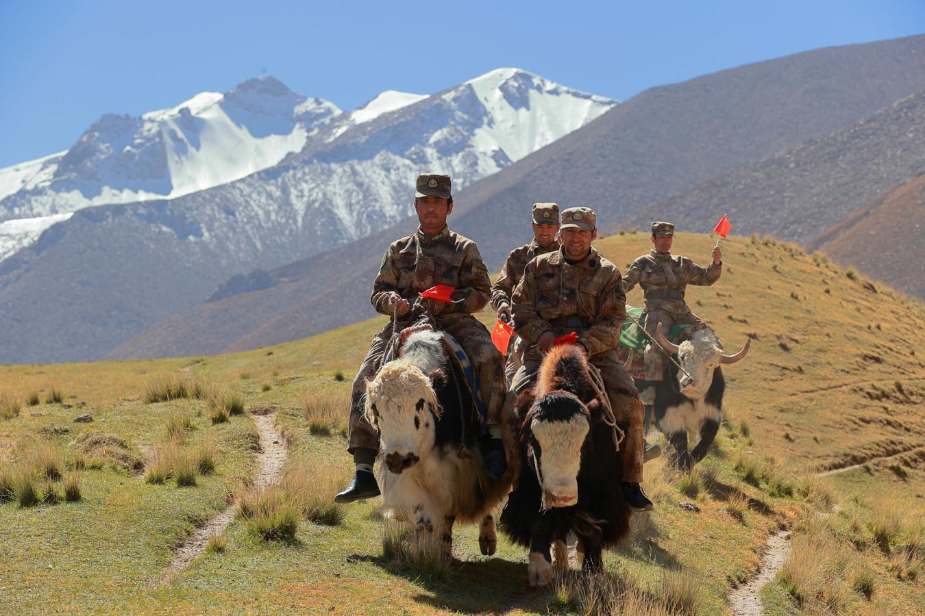 Soldaten patrouilleren op yaks in Xinjiang, waar volgens de regering in Peking 'alle mensen eendrachtig samen, in harmonie en solidariteit' wonen.