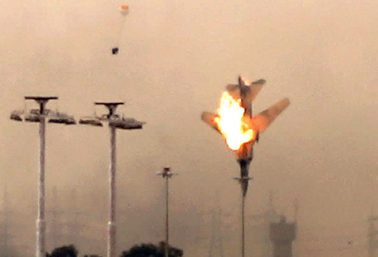 Een neerstortende straaljager bij Benghazi. Het vliegtuig is waarschijnlijk van troepen van Kadhafi, de piloot kon nog ontkomen (zwarte stip linksboven). Beeld afp
