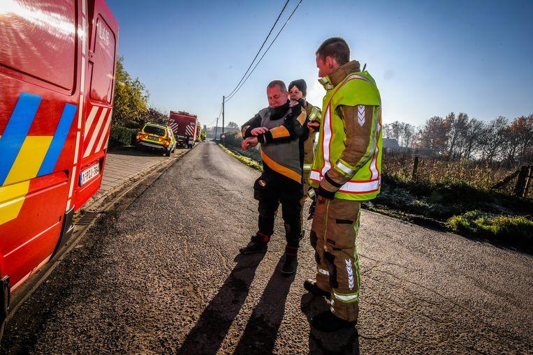 Een duiker van de brandweer doet zijn pak aan om het lichaam uit de waterplas te halen.