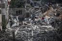 Palestijnen bij de resten van een gebouw dat werd getroffen door de Israëlische luchtmacht.