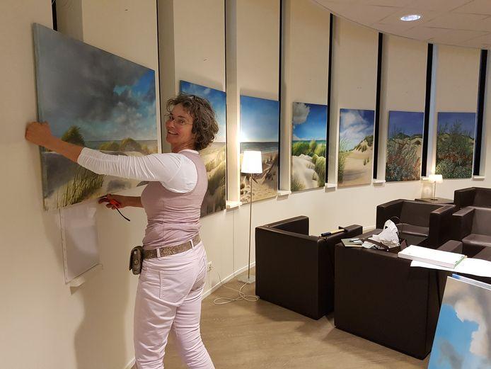 Mirella Damen bij de schilderijen die ze heeft gemaakt van de Zeeuwse kust. Ze hangen nog een week in de leeszaal van de Zevenbergse bibliotheek.
