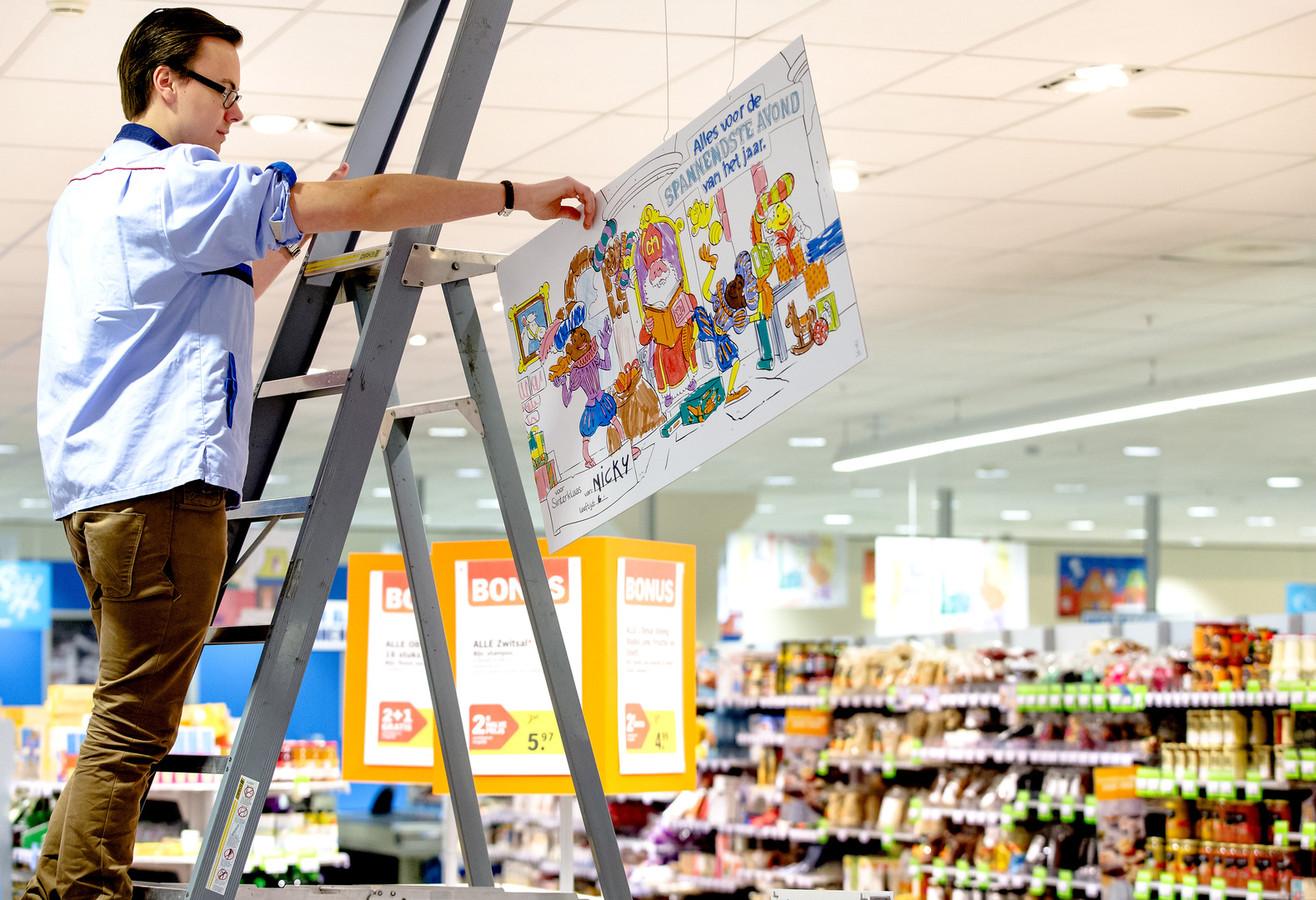 Een medewerker van Albert Heijn in 2014. Hij hangt een kleurplaat op om het filiaal te versieren voor Sinterklaas