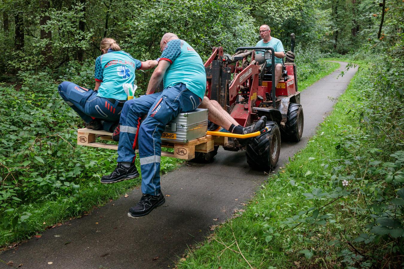 Diederik Groen brengt per shovel de gewonde man naar de ambulance, samen met het ambulancepersoneel.