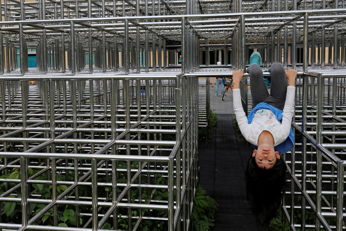 Een Taiwanees meisje hangt aan een stalen junglestelling in een speeltuin in Taipei. Foto Tyrone Siu