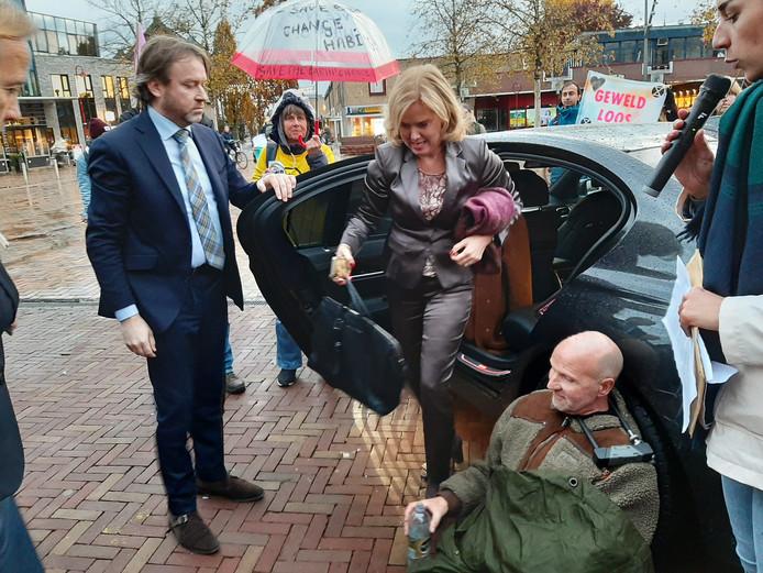 Vinkevener Cor Mastwijk heeft zich aan de dienstauto van minister Cora van Nieuwenhuizen vastgeketend. De minister haalt haar tas en jas uit de auto omdat ze niet weg kan naar haar volgende afspraak. De chauffeur houdt het portier open voor de excellentie.