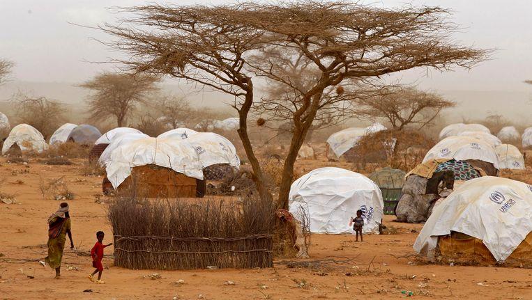 Vluchtelingen wandelen langs hutjes in het vluchtelingenkamp in Dadaab. Beeld AP