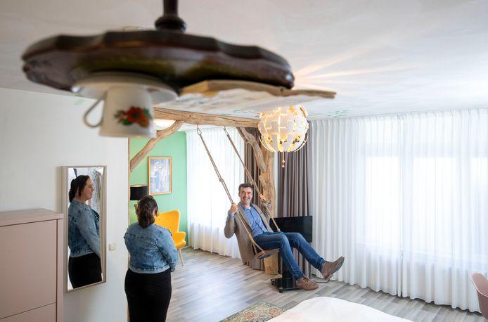 Hotelmanager Hans Hooft test de schommel uit in de themakamer over Astrid Lindgren onder het toeziend oog van gastvrouw Henriet van Wolfswinkel.
