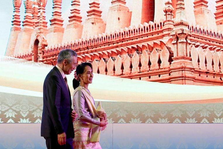 De opgesloten regeringsleider Aung San Suu Kyi, hier met de premier van Singapore in 2016, maakt deel uit van de eenheidsregering en zou daarvan op de hoogte zijn. Beeld REUTERS