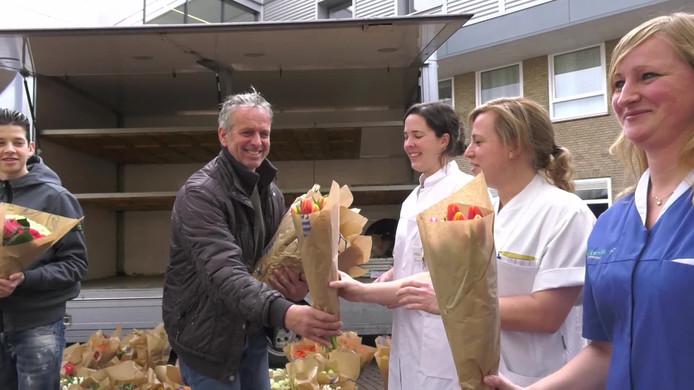Bloemenhandelaar Fred Magendans uit Eindhoven deelt bloemen uit bij het Elkerliek Ziekenhuis in Helmond.