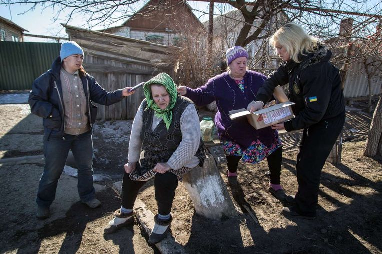 Oekraïense vrijwilligers delen pakketten uit in Luganske, vlakbij Debaltseve. Beeld AFP