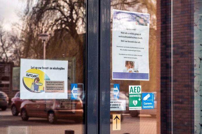 Briefjes op de voordeur van een verpleeghuis om bezoekers te waarschuwen voor de coronaregels, foto ter illustratie.