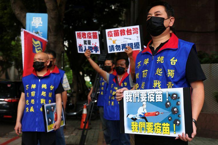 Mensen manen met protestborden de Taiwanese overheid de vaccins uit China te accepteren.   Beeld REUTERS