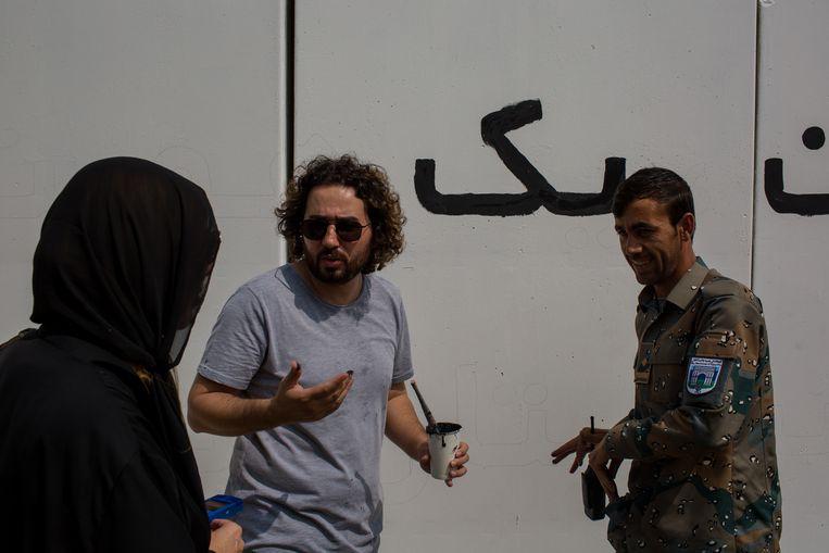 Omaid Sharifi krijgt bezoek van politieman Assadullah.'De politie staat in voor de veiligheid, dus ik ga zeker stemmen.' Beeld Yan Boechat