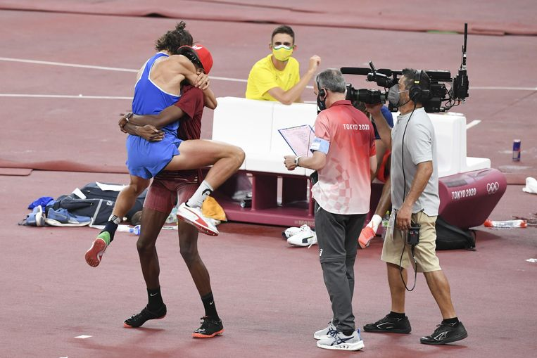 Gianmarco Tamberi springt Mutaz Essa Barshim in de armen nadat ze horen dat ze allebei goud hebben gewonnen. Beeld EPA