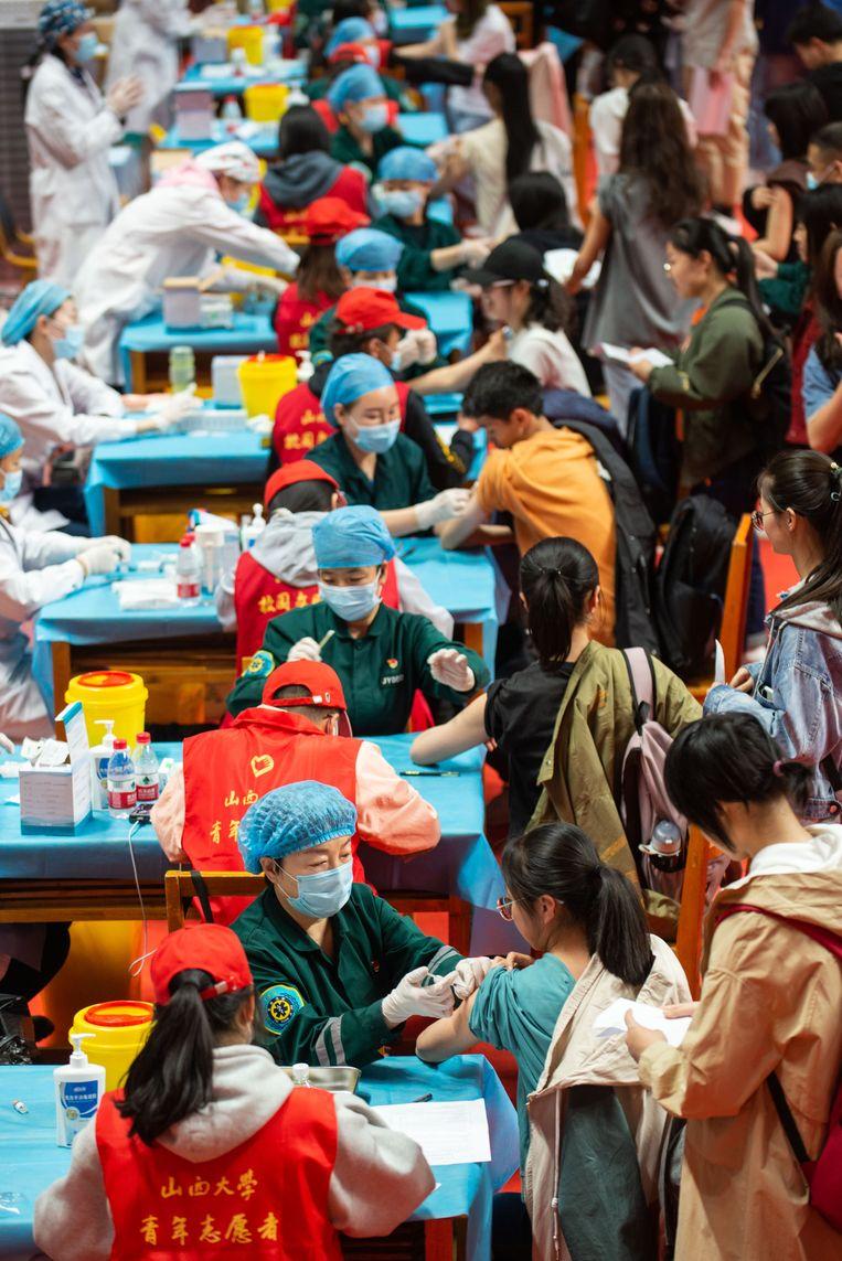Studenten en docenten van de Shanxi Universiteit in Taiyuan staan in de rij om te worden ingeënt met een covid-19-vaccin. Beeld China News Service via Getty