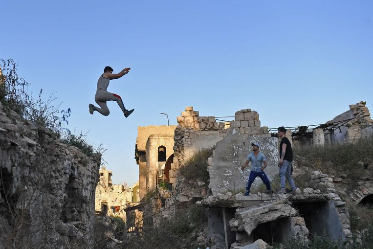 TOPSHOT - Syrian youths practice parkour in Aleppo, northern Syria, on April 7, 2018. The government retook full control of Aleppo from rebel-fighters in December 2016. / AFP PHOTO / George OURFALIAN Beeld AFP