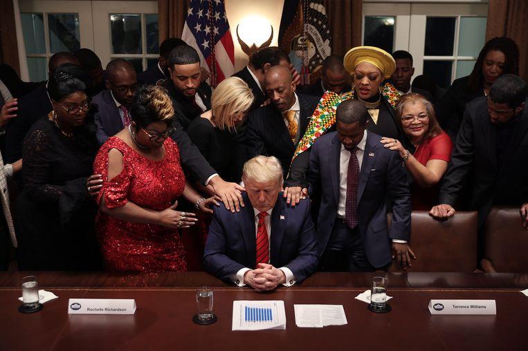 Gezamenlijk gebed, 27 februari 2020: Zwarte Trumpaanhangers bidden met hem in het Witte Huis, na een bijeenkomst waarin hij sprak over de goede economische resultaten die hij heeft bereikt voor de zwarte Amerikaanse gemeenschap. Beeld Getty Images