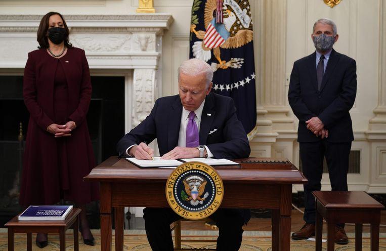 President Biden tekent presidentiële besluiten in het Witte Huis. Beeld AFP