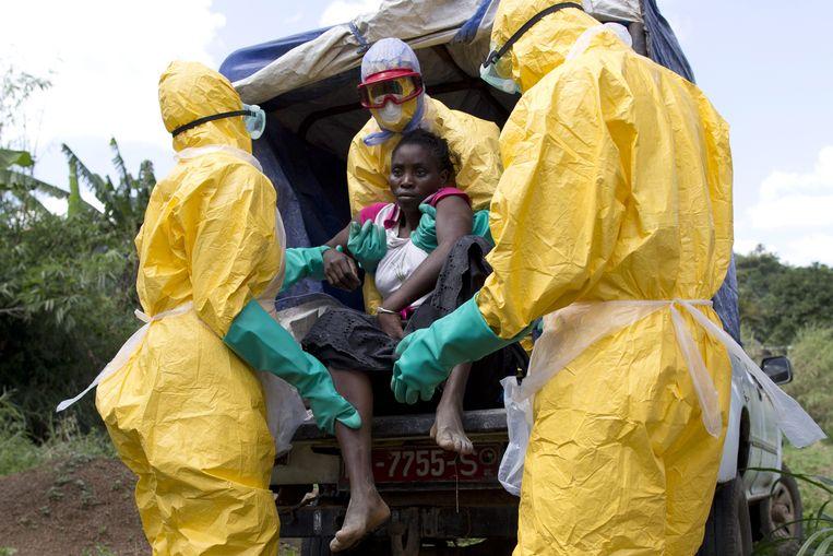 Hulpverleners in Guinee helpen een vrouw die mogelijk besmet is met Ebola. Beeld AFP