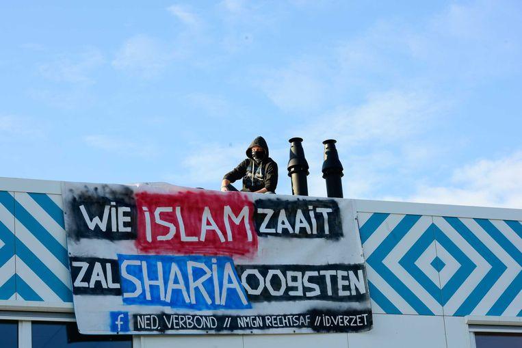 September 2017: Twee mannen protesteren op het dak van de nieuwe middelbare islamitische school in de Amsterdamse wijk Nieuw-West. Beeld ANP