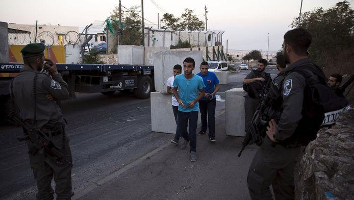 Israëlische soldaten bewaken een nieuw geplaatst checkpoint. Palestijnse jongeren passeren.