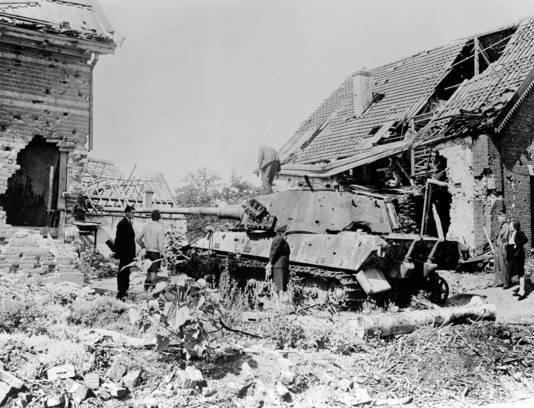 Overlevenden van de Slag om Arnhem in 1945 bij een Duitse Tiger-tank in de Weverstraat in Oosterbeek.