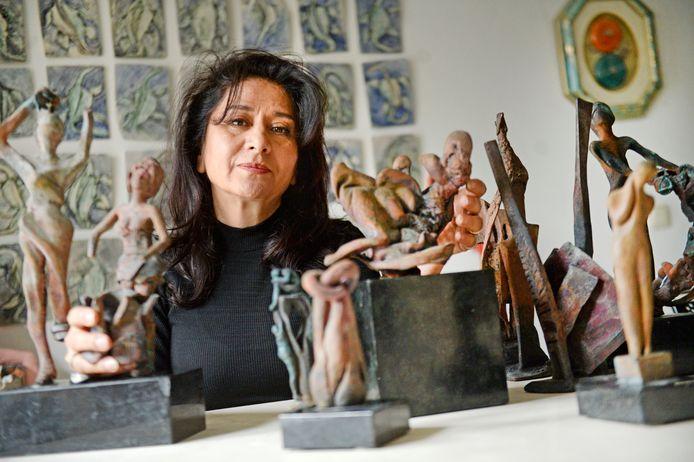 Kunstenares Persheng Warzandegan met de bronzen beeldjes die als enige uit haar verwoeste huis kwamen.