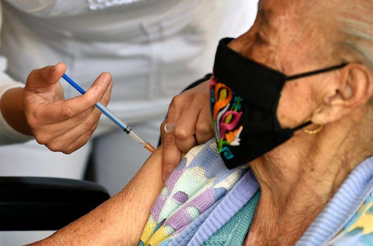 Een vrouw in Mexico-Stad wordt ingeënt met het Pfizer-vaccin (de echte). Beeld AFP