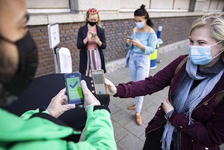 Bezoekers tonen hun negatieve coronatest voordat ze naar binnengaan bij de Heineken Experience.  Beeld ANP