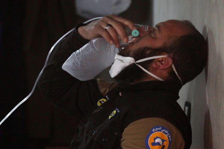 Een hulpverlener dient zichzelf zuurstof toe na de vermoedelijke gifgas-aanval in Idlib.  Beeld REUTERS