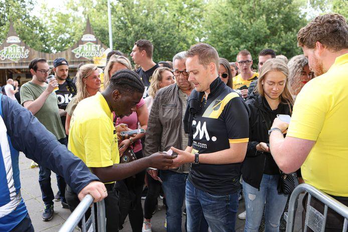 Met een biertje in de hand wachten supporters netjes in de rij voor de toegangscontrole.