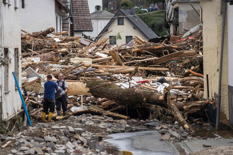 Twee mannen halen spullen weg uit een verwoest huis in het dorp Schuld. Beeld AFP