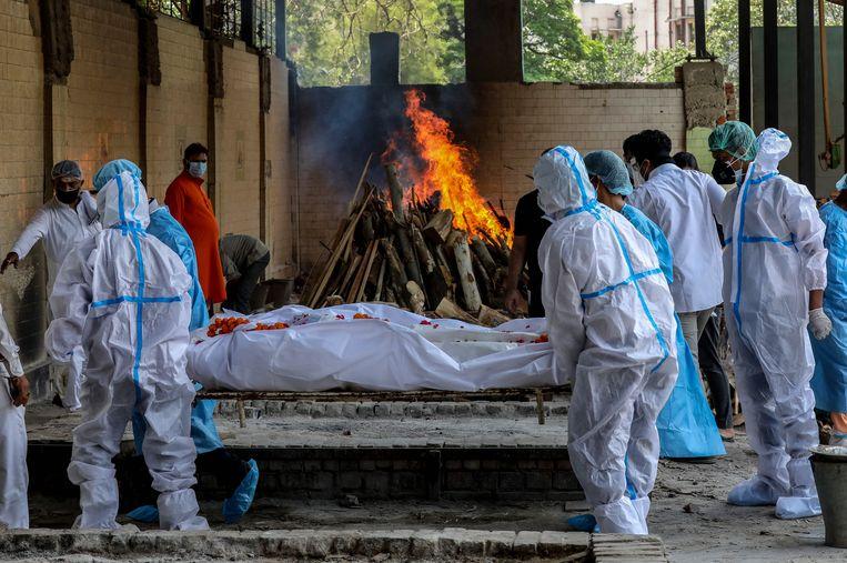 Begrafenisceremonie van een covidslachtoffer in India, een van de landen waar de situatie nijpend is. Beeld EPA
