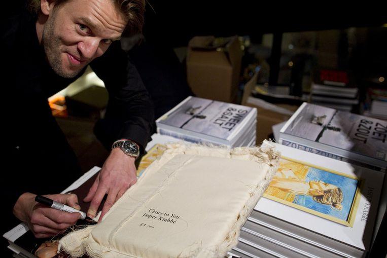 Schilder Jasper Krabbe signeert tijdens de opening van de tentoonstelling Closer to You in De Kunsthal in Rotterdam. Beeld