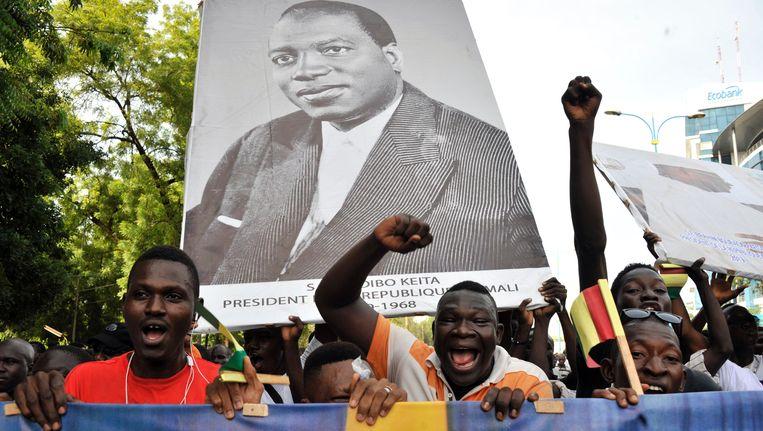 Demonstranten houden in Bamako het portret van Mali's eerste president Modibo Keita omhoog, terwijl ze met duizenden anderen deelnemen aan een mars om de huidige president Ibrahim Boubacar Keita te steunen Beeld AFP