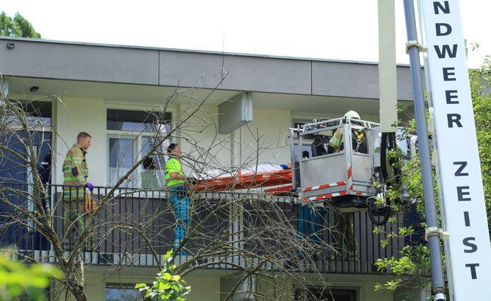 De brandweer takelt de gevallen man uit zijn woning.