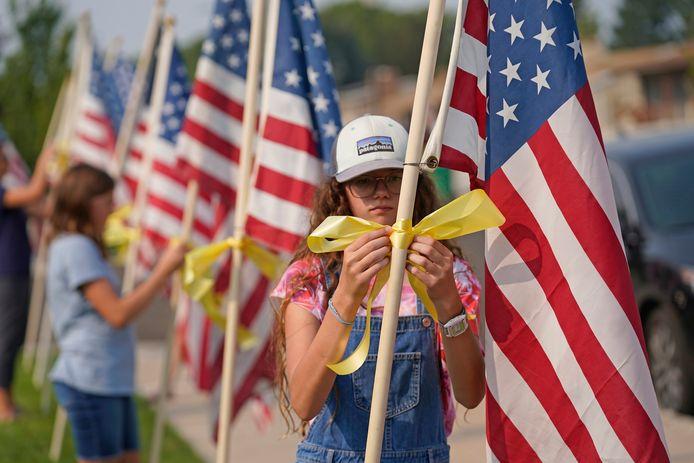 Buurtbewoners van het ouderlijke huis van Taylor Hoover in Sandy (Utah) plaatsen Amerikaanse vlaggen. (1/2)