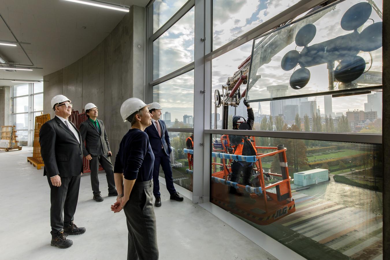 Directeur Roelof Prins van stichting De Verre Bergen, museumdirecteur Sjarel Ex, architect Fokke Moerel van MVRDV en wethouder Bas Kurvers (v.l.n.r.) bekijken hoe het laatste glaspaneel tegen het glimmende kunstdepot wordt gezet.