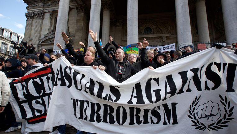 Honderden hooligans trokken gisteren naar het Brusselse Beursplein, waar verschillenden van hen de Hitlergroet brachten. Beeld BELGA